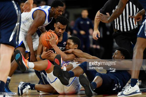 Charlie Moore of the DePaul Blue Demons battles for the basketball against Paul Scruggs and Quentin Goodin of the Xavier Musketeers in the second...