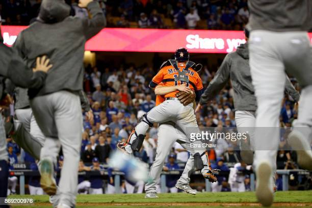 Charlie Morton and Brian McCann of the Houston Astros celebrate after defeating the Los Angeles Dodgers in game seven with a score of 5 to 1 to win...