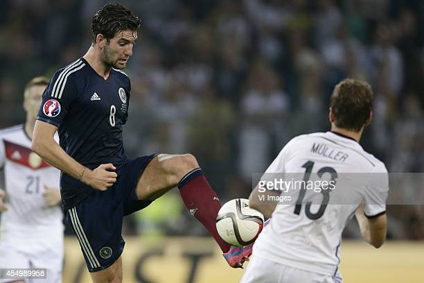 Charlie Mulgrew of Scotland Thomas Muller of Germany during the EURO 2016 qualifying match between Germany and Scotland on September 7 2014 at the...