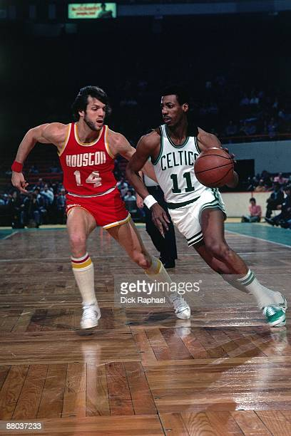 Charlie Scott of the Boston Celtics drives to the basket against Mike Newlin of the Houston Rockets during a game played in 1976 at the Boston Garden...