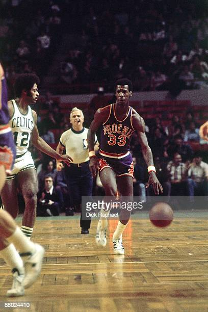 Charlie Scott of the Phoenix Suns moves the ball up the court against Don Chaney of the Boston Celtics during a game played in 1975 at the Boston...