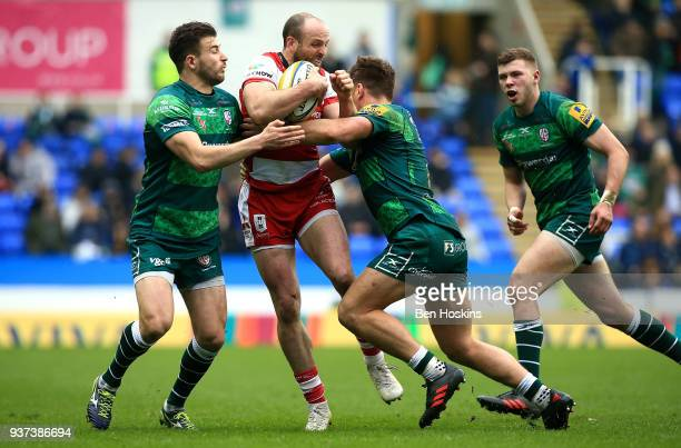 Charlie Sharples of Gloucester is tackled by Tommy Bell and Alex Lewington of London Irish during the Aviva Premiership match between London Irish...