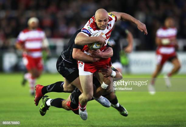 Charlie Sharples of Gloucester Rugby is tackled by Michael Young of Newcastle Falcons during the Aviva Premiership match between Newcastle Falcons...