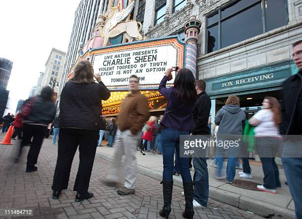 "Charlie Sheen fans pose for pictures in front of the Fox Theatre in Detroit, Michigan on April 2, 2011 to start his show ""Violent Torpedo of..."