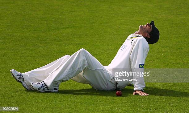 Charlie Shreck of Nottinghamshire looks skyward after hurting his right knee during the LV County Championship Division One match between Durham and...