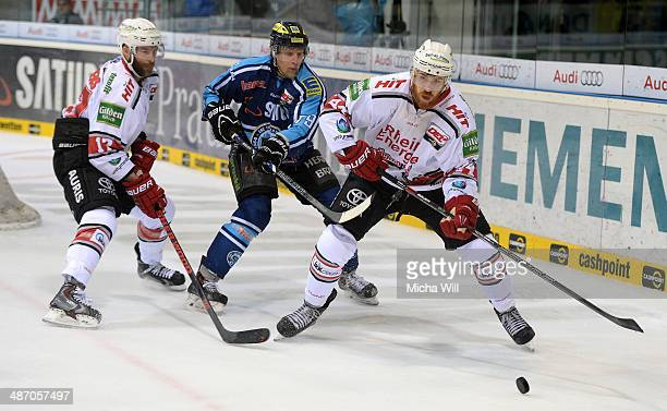 Charlie Stephens of Koeln Greg Claassen of Ingolstadt and Bjoern Krupp of Koeln compete for the puck in game six of the DEL final playoffs between...