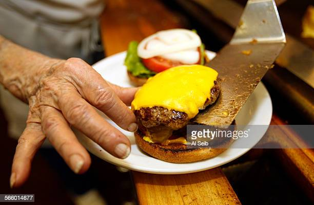 Charlie Sue Gilbert owner of Charlie's Coffee Shop at the Third and Fairfax Farmer's Market in Los Angeles prepares her renowned cheeseburger on...