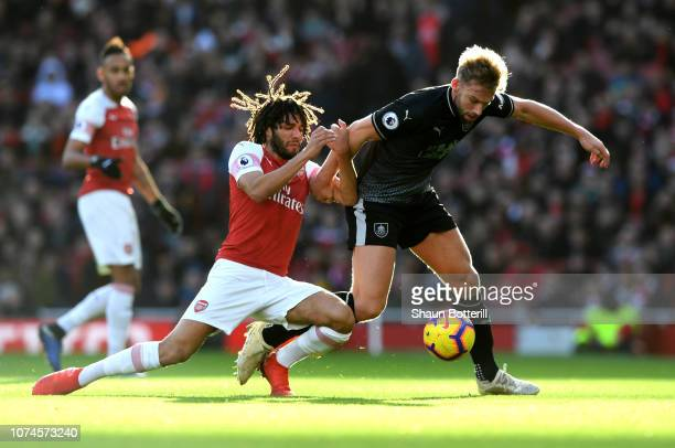 Charlie Taylor of Burnley is challenged by Mohamed Elneny of Arsenal during the Premier League match between Arsenal FC and Burnley FC at Emirates...