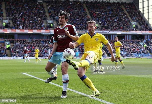 Charlie Taylor of Leeds clears the ball from Joey Barton of Burnley during the Sky Bet Championship match between Burnley and Leeds United at Turf...