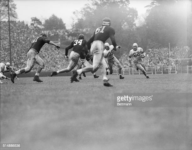 Charlie Trippi #62 runs to the right seeking a pass receiver as Mel Bray blocks out an Alabama player Trippi couldn't find a receiver and elected to...
