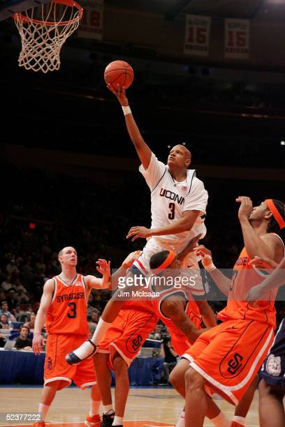 Charlie Villanueva of the Connecticut Huskies goes over Darryl Watkins of the Syracuse Orangemen for a shot during the semifinal round of the Big...