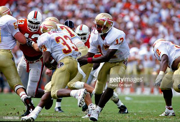 Charlie Ward of the Florida State Seminoles hands the ball of to Tiger McMillen against the University of Miami during an NCAA football game at the...