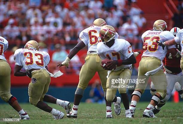Charlie Ward of the Florida State Seminoles rolls out to pass against the University of Miami during an NCAA football game at the Orange Bowl October...