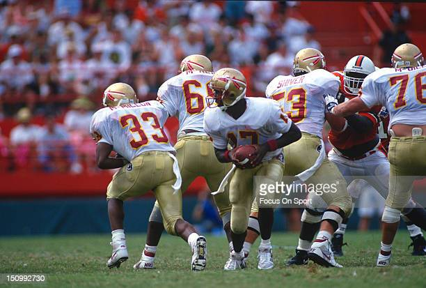 Charlie Ward of the Florida State Seminoles turns to hand the ball off against the University of Miami during an NCAA football game at the Orange...