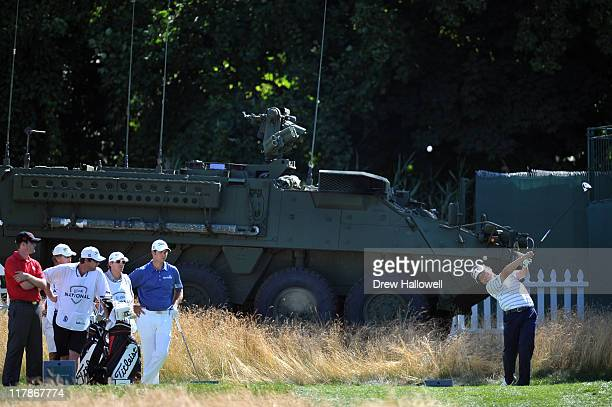 Charlie Wi hits his tee shot on the ninth hole in front of a US Army Stryker during the second round of the ATT National at Aronimink Golf Club on...