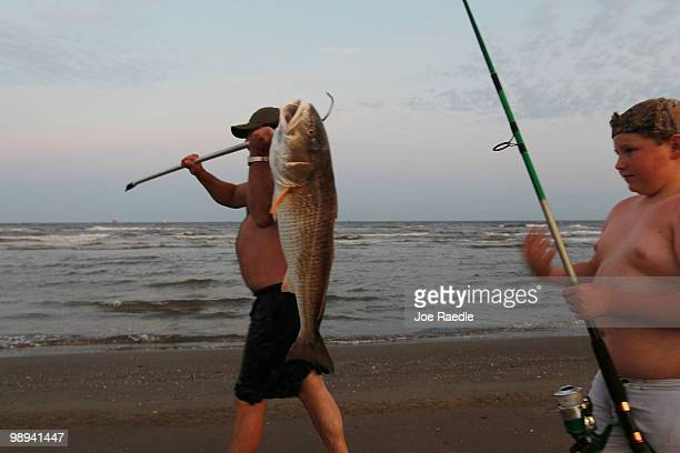 Charlie Wyers carries a fish that his son Zachary Wyers caught in the gulf waters as efforts continue to contain the massive oil spill on May 9 2010...