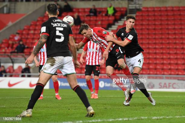 Charlie Wyke of Sunderland scores their side's first goal as he battles with Lewis Montsma of Lincoln City during the Papa John's Trophy Semi-Final...