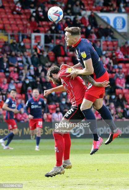 Charlie Wyke of Sunderland wins a header against Adam Jackson off Lincoln during the Sky Bet League One Play-off Semi Final 1st Leg match between...