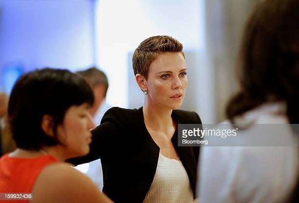 Charlize Theron a Hollywood actress and celebrity speaks with colleagues during a break at the on the opening day of the World Economic Forum in...