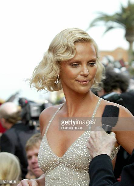Charlize Theron speaks to the media as she arrives for the 76th Academy Awards ceremony 29 February 2004 at the Kodak Theater in Hollywood CA Theron...
