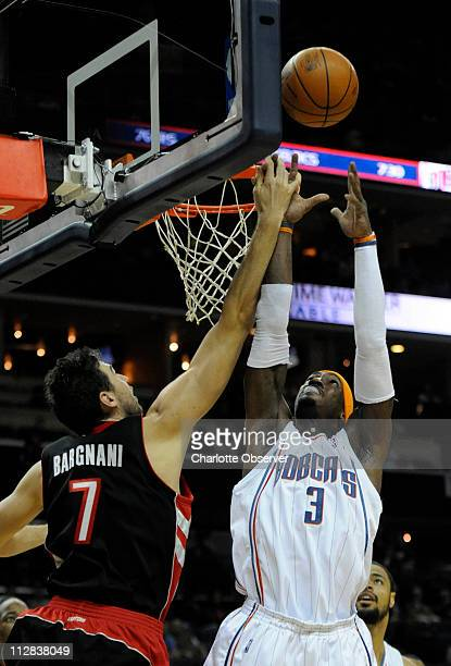 Charlotte Bobcats' Gerald Wallace claims a rebound over Toronto Raptors' Andrea Bargnani in the first half of play at Time Warner Cable Arena in...