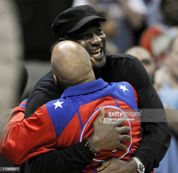 Charlotte Bobcats managing partner Michael Jordan hugs Harlem Globetrotters' Fred Curly Neal during the first half of the Bobcats' game against the...