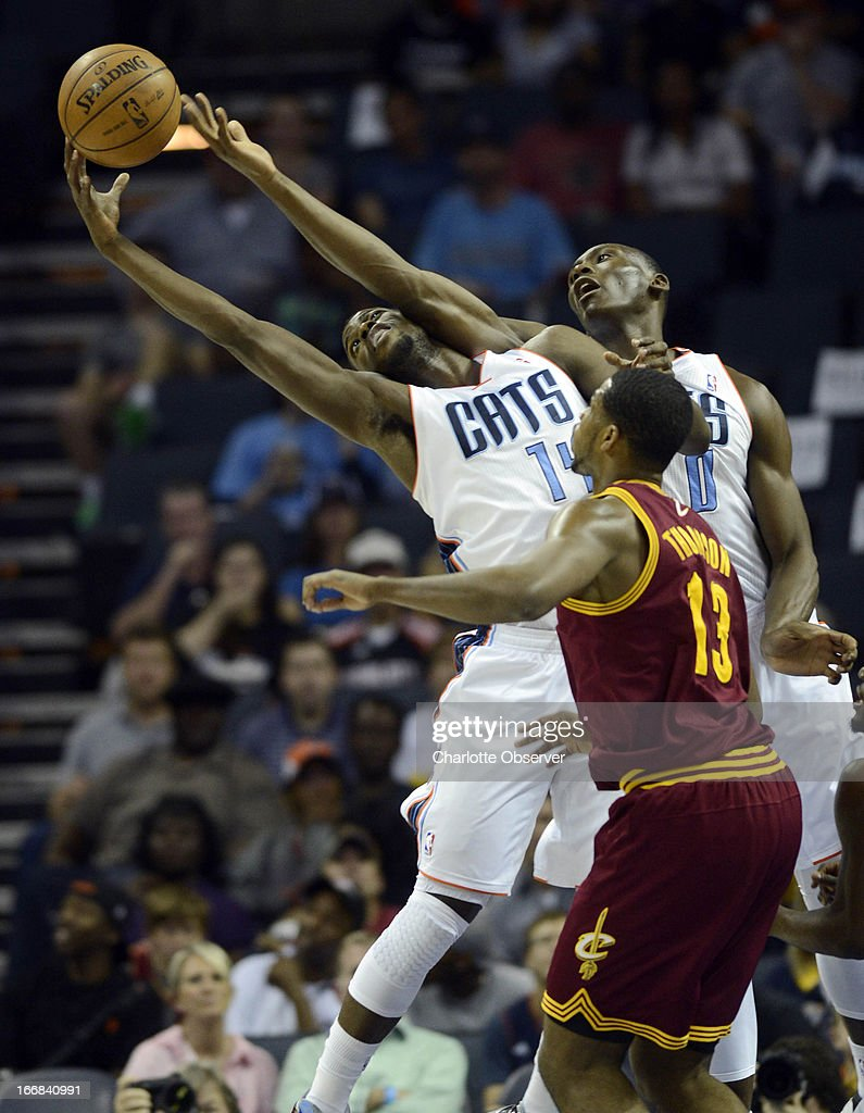 Charlotte Bobcats' Michael Kidd-Gilchrist (14) and Bismack Biyombo (0) reach for a rebound as Cleveland Cavaliers' Tristan Thompson (13) eyes the ball during the first half at Time Warner Cable Arena in Charlotte, North Carolina, Wednesday, April 17, 2013.