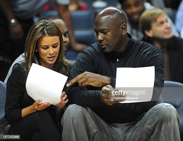 Charlotte Bobcats owner Michael Jordan and his fiance Yvette Prieto look over stat sheets following firstquarter action against the Cleveland...