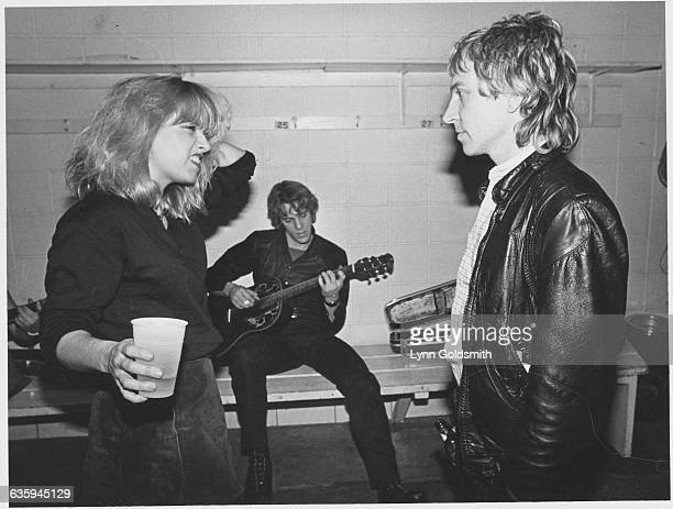 Charlotte Caffey of the GoGo's speaks to Andy Summers of the Police while Stewart Copeland plays guitar