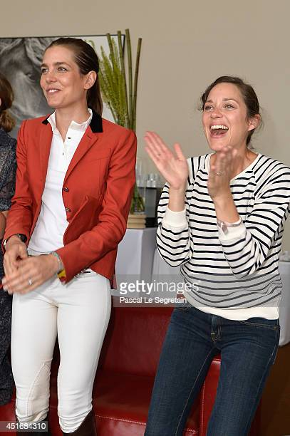 Charlotte Casiraghi and Marion Cotillard attend the Paris Eiffel Jumping presented by Gucci at ChampdeMars on July 4 2014 in Paris France