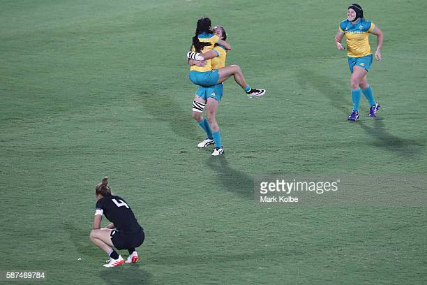 Charlotte Caslick Chloe Dalton and Sharni Williams of Australia celebrate victory as Niall Williams of New Zealand looks dejected after the Women's...