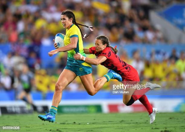 Charlotte Caslick of Australia is tackled by Jasmine Joyce of Wales during the Rugby Sevens Women's Pool B match between Australia and Wales on day...