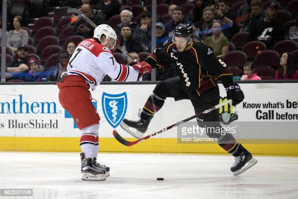 Charlotte Checkers C Aleksi Saarela and Cleveland Monsters D John Ramage battle for the puck during the first period of the AHL hockey game between...