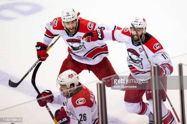 Charlotte Checkers center Clark Bishop and Charlotte Checkers center Nicolas Roy celebrate Charlotte Checkers right wing Zach Nastasiuk's goal during...