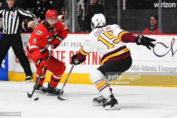 Charlotte Checkers center Nicolas Roy works the puck against Chicago Wolves defenseman Dylan Coghlan during game two of the AHL Calder Cup Finals...