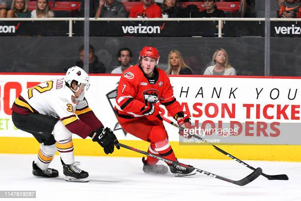Charlotte Checkers left wing Aleksi Saarela keeps the puck out of reach from Chicago Wolves defenseman Zach Whitecloud during game one of the Calder...