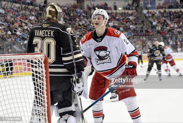 Charlotte Checkers right wing Julien Gauthier smiles as Hershey Bears goalie Vitek Vanecek sets a pick and tries to block his path to to behind the...