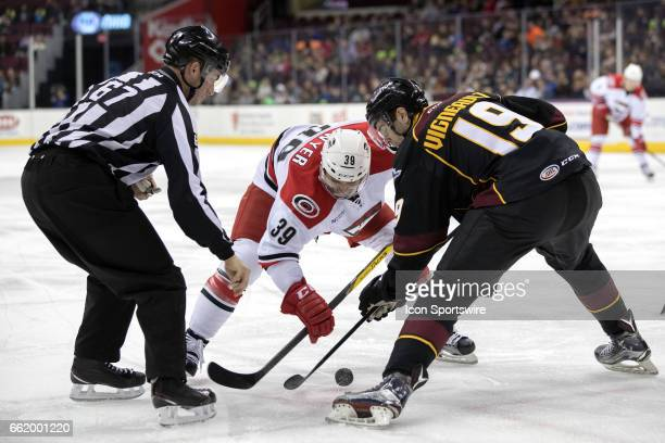 Charlotte Checkers RW Patrick Dwyer and Cleveland Monsters C Sam Vigneault battle for a faceoff during the first period of the AHL hockey game...