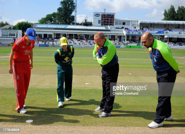 Charlotte Edwards of England tosses the coin and views the result with Jodie Fields of Australia and the umpires during the England Women and...