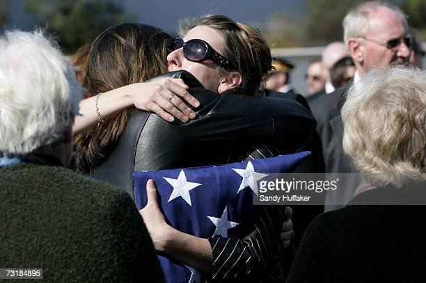 Charlotte Freeman hugs a friend at the funeral of her husband Captain Brian Freeman during a memorial service at Ft Rosecrans National Cemetery on...