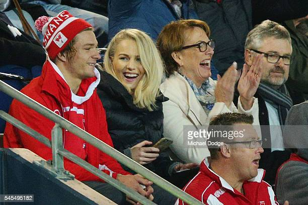 Charlotte Goodlet girlfriend of Kieran Jack of the Swans sits next to Brandon Jack during the round 16 AFL match between the Geelong Cats and the...