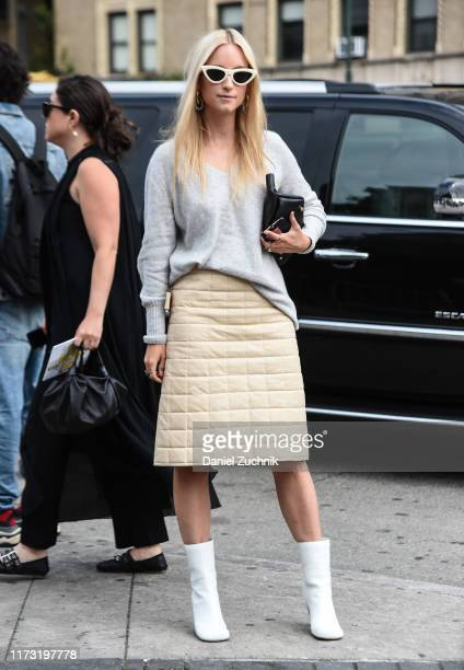 Charlotte Groeneveld is seen wearing a gray sweater beige skirt and white boots outside the Tory Burch show during New York Fashion Week S/S20 on...