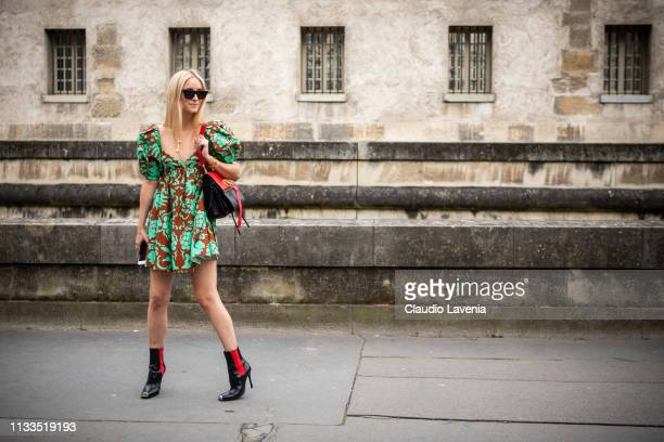 Charlotte Groeneveld, wearing a green and brown mini dress, black boots and black and red Valentino bag, is seen outside Valentino on Day 7 Paris...