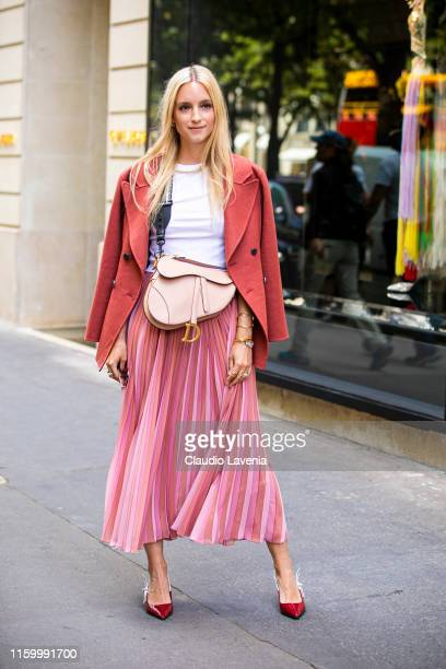 Charlotte Groeneveld, wearing a white t-shirt, pink midi skirt, nude Dior bag, red Dior heels and red coat, is seen outside Christian Dior show...