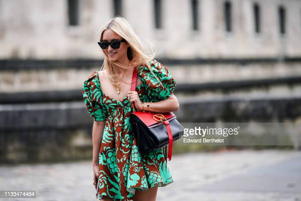 Charlotte Groeneveld wears a green and brown floral print dress, a red and black Valentino bag, red and black heels shoes, outside Valentino, during...