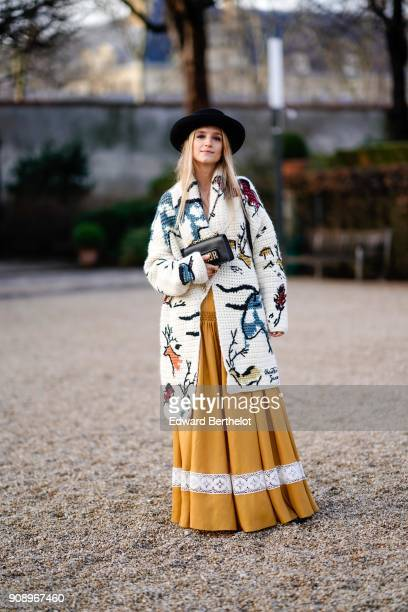 Charlotte Groeneveld wears a hat a white coat with colored features a yellow pleated dress with a white stripe after Dior during Haute Couture...