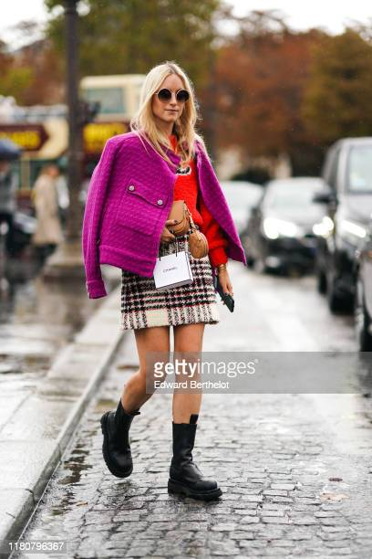 Charlotte Groeneveld wears a purple wool jacket a red pullover a checked skirt a light brown bag sunglasses outside Chanel during Paris Fashion Week...