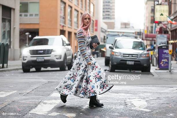 Charlotte Groeneveld wears a Valentino outfit including a white floral pleated windmill dress with striped sleeves a black purse and black boots...
