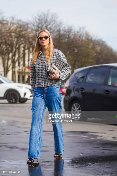 Charlotte Groeneveld wears sunglasses, a black and white checked tweed jacket, blue denim flared jeans, shoes, outside Chanel, during Paris Fashion...