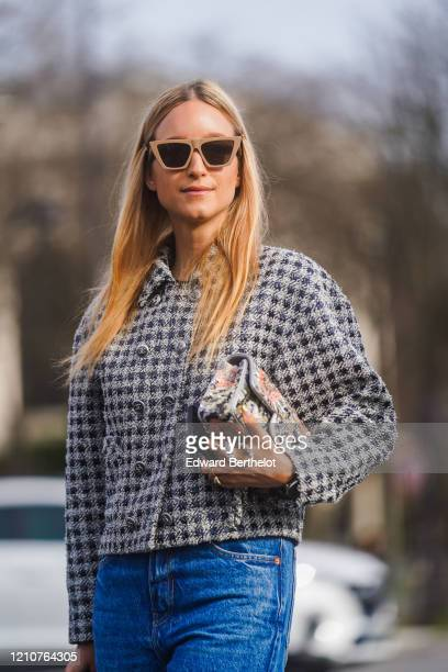 Charlotte Groeneveld wears sunglasses, a black and white checked tweed jacket, blue denim flared jeans, outside Chanel, during Paris Fashion Week -...